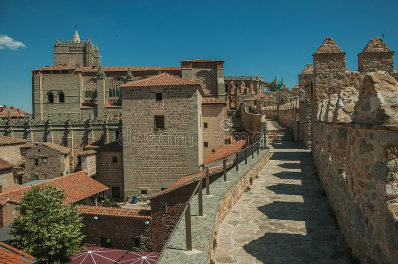 Pathway over wall around the town and Cathedral of Avila. Pathway over thick stone wall with battlement around the town and side view of Cathedral at Avila. It royalty free stock images