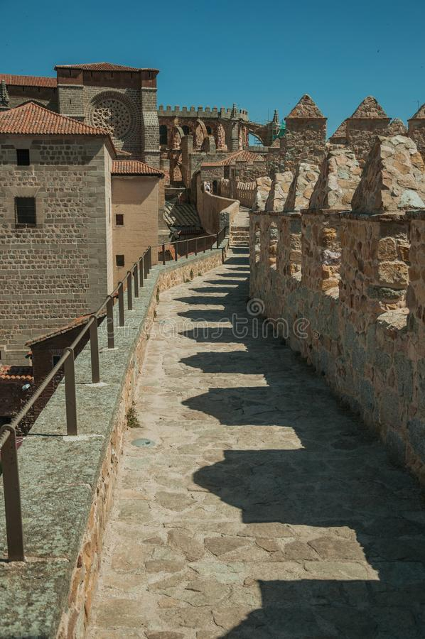 Pathway over wall around the town and Cathedral of Avila. Pathway over thick stone wall with battlement around the town and side view of Cathedral at Avila. It royalty free stock photos