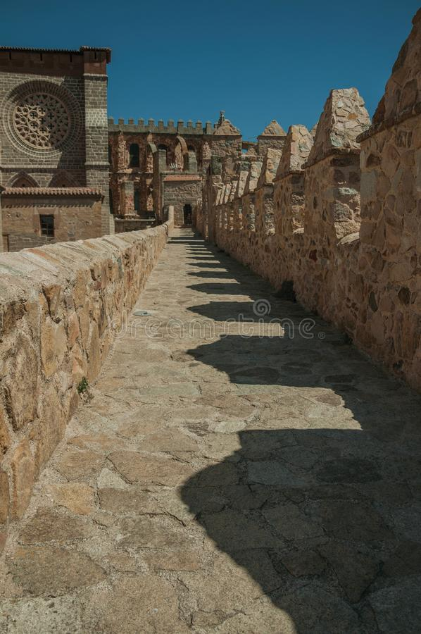Pathway over wall around the town and Cathedral of Avila. Pathway over thick stone wall with battlement around the town and side view of Cathedral at Avila. It stock photography