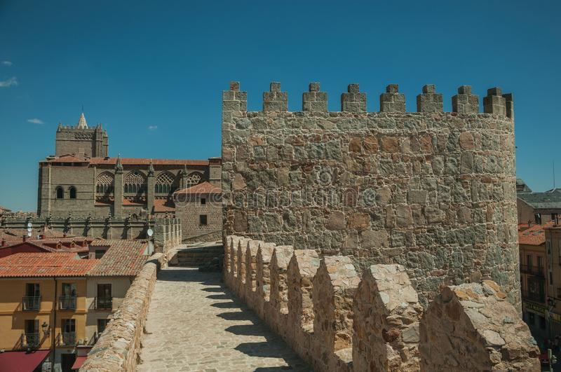 Pathway over wall around the town and Cathedral of Avila. Pathway over thick stone wall with battlement around the town and side view of Cathedral at Avila. It royalty free stock image