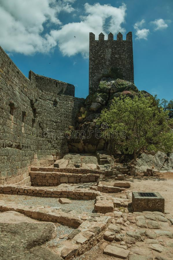 Pathway over wall and tower from keep in a castle. Thick stone wall with square tower from keep in front of green rocky courtyard, in a sunny day at the Sortelha royalty free stock photo