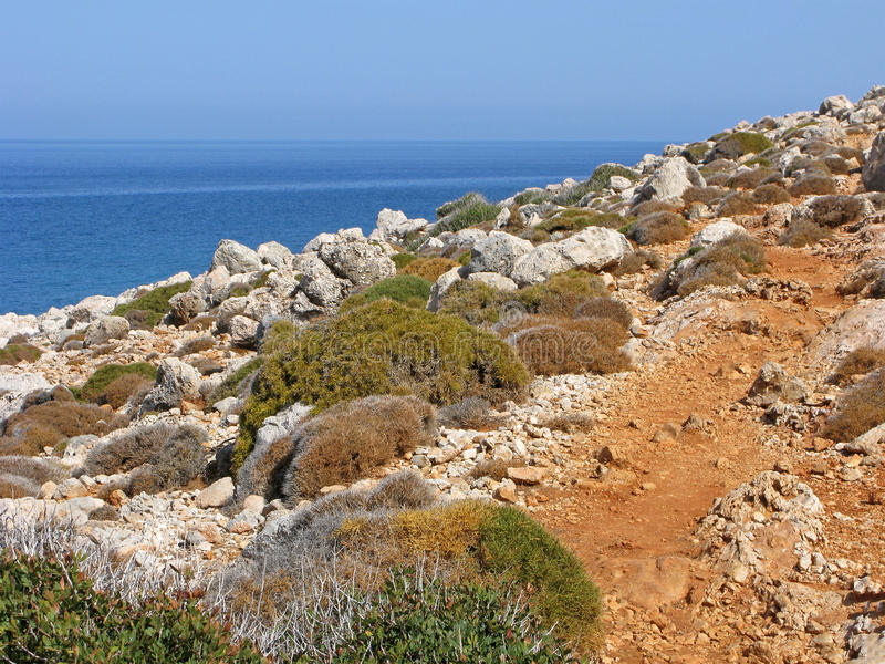 Pathway on rocky cliff above blue sea stock photo