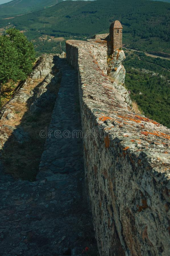 Pathway on stone wall with watchtower over ridge in Marvao stock photo