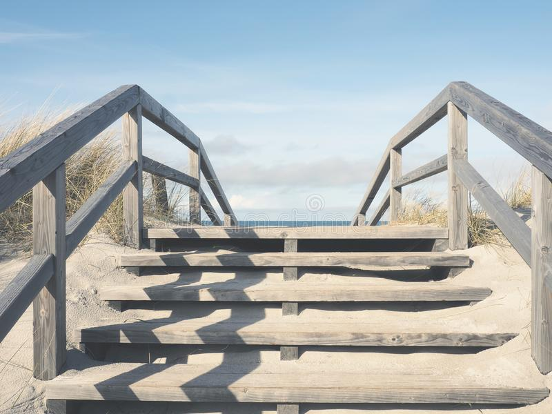 Pathway to the beach on a sunny morning. Dune with wooden stairs, pathway to the beach, sunny winter morning stock image