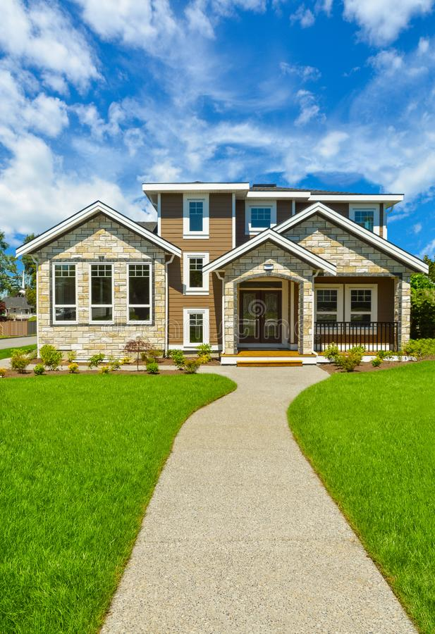 Pathway to Ideal residential house in perfect neighbourhood. Family house with big green lawn in front on blue sky background stock photography