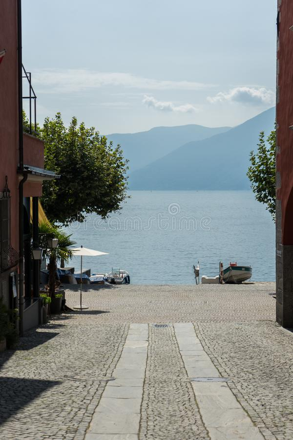 Pathway to lago maggiore with water and mountain view in ascona switzerland. At summer day stock photo