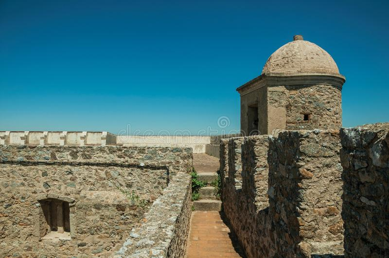 Pathway on top of stone wall with tower at the Castle of Elvas. Pathway on top of thick stone wall with tower and merlons in sunny day at the Castle of Elvas. A stock image