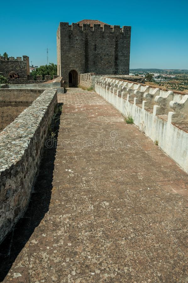 Pathway on top of stone wall with tower at the Castle of Elvas. Pathway on top of thick stone wall with tower and merlons in sunny day at the Castle of Elvas. A royalty free stock image