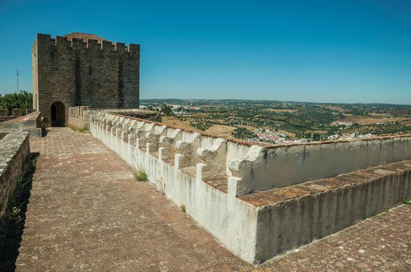 Pathway on top of stone wall with tower at the Castle of Elvas. Pathway on top of thick stone wall with tower and merlons in sunny day at the Castle of Elvas. A royalty free stock photography