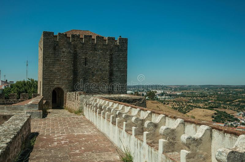 Pathway on top of stone wall with tower at the Castle of Elvas. Pathway on top of thick stone wall with tower and merlons in sunny day at the Castle of Elvas. A stock photo