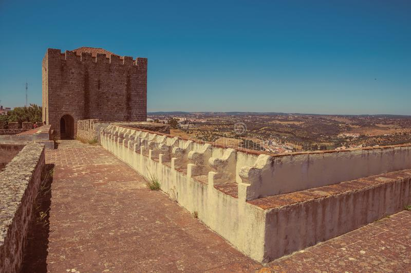 Pathway on top of stone wall with tower at the Castle of Elvas. Pathway on top of thick stone wall with tower and merlons in sunny day at the Castle of Elvas. A royalty free stock photo
