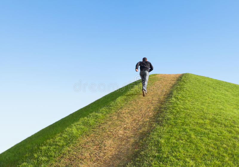 Pathway up the hill. Man ran to the top. royalty free stock photography