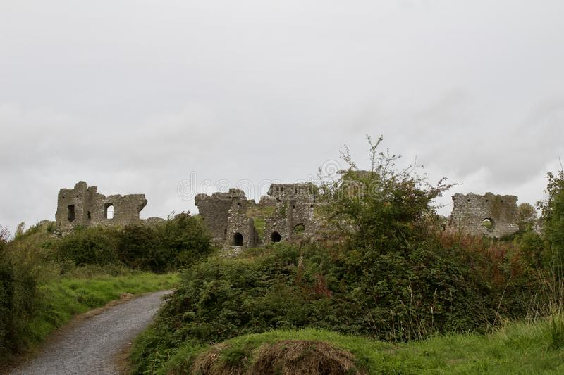 Pathway up to Medieval castle ruins in rural Ireland on an overcast day royalty free stock photos