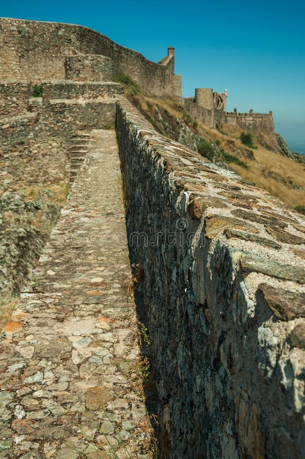Pathway on wall and tower over rocky hill at the Marvao Castle. Close-up of pathway on thick stone wall and square tower over rocky hill, in a sunny day at the royalty free stock photography