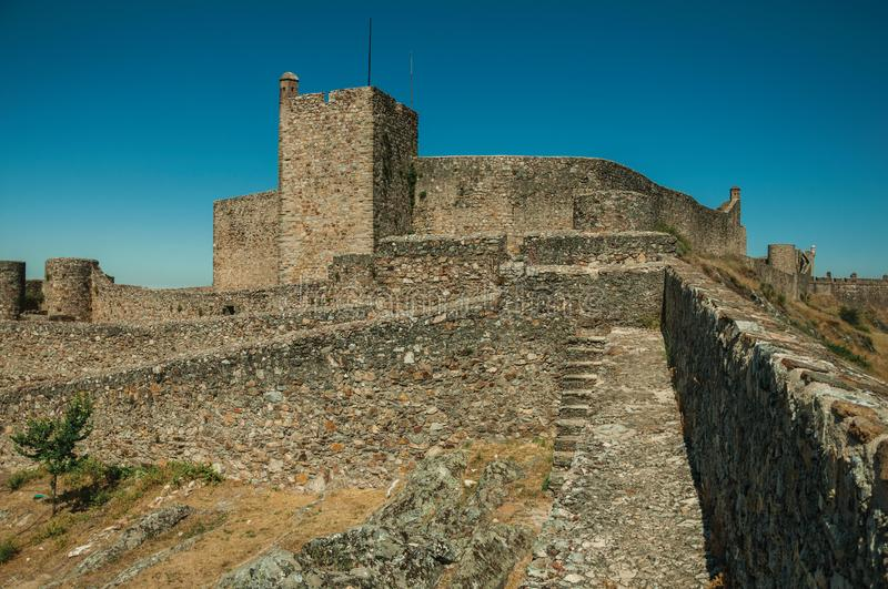 Pathway on wall and tower over rocky hill at the Marvao Castle. Close-up of pathway on thick stone wall and square tower over rocky hill, in a sunny day at the stock photography