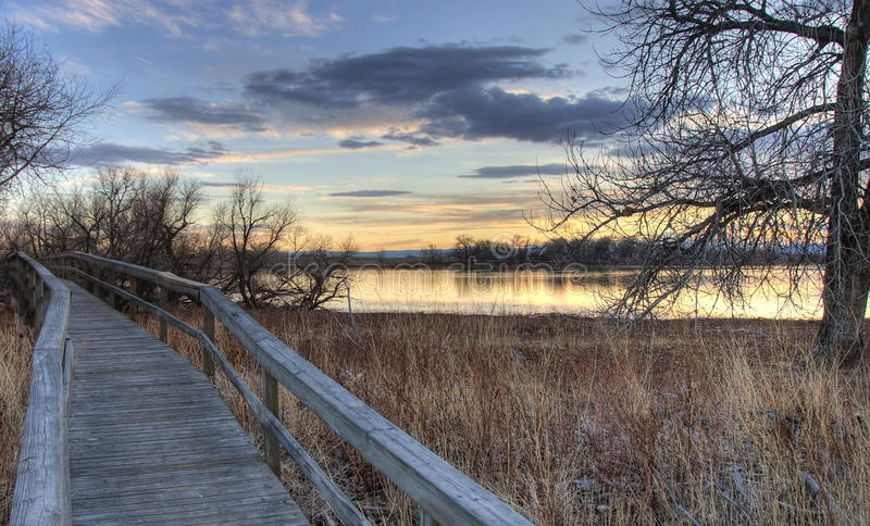 Pathways. Walking bridge adjacent a Colorado lake just before sunset royalty free stock photos