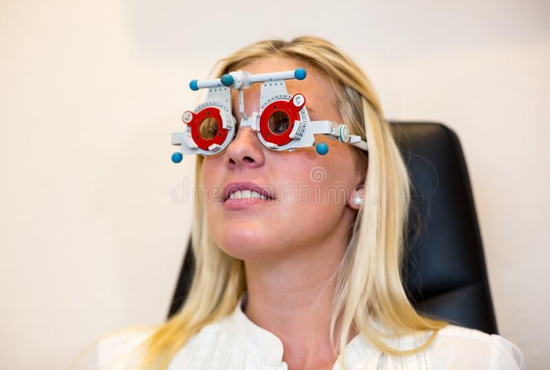 Patiënt bij optometrist met proefkader voor testglazen royalty-vrije stock fotografie