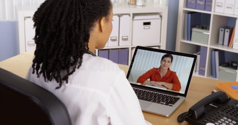 Patiënt die aan Afrikaanse Amerikaanse arts over videopraatje spreekt royalty-vrije stock foto's