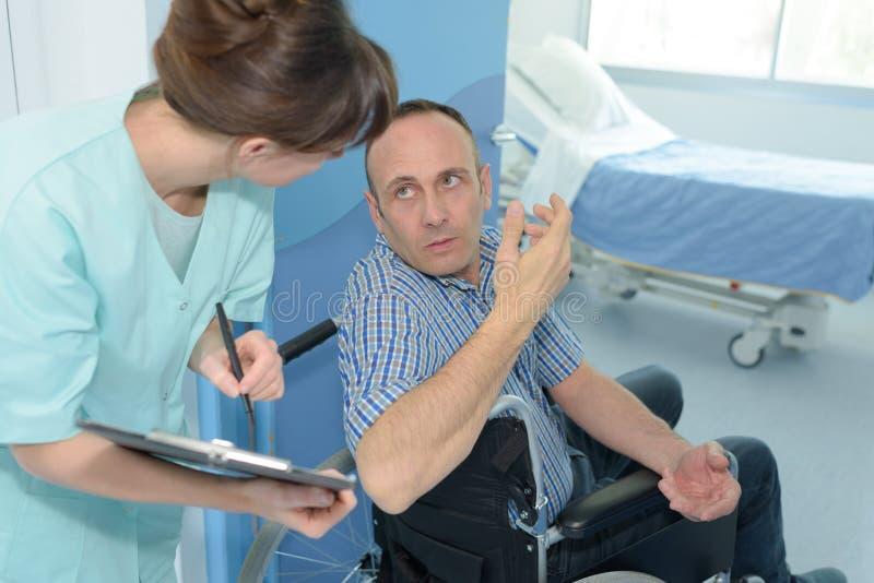 Patiënt die aan verpleegster spreken alvorens ruimte in te gaan stock afbeelding