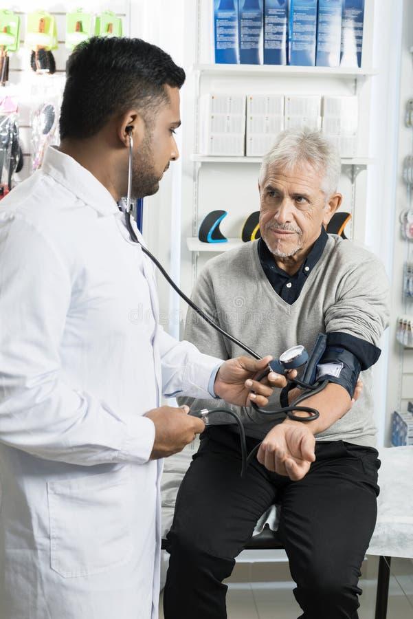 Patiënt die Chemicus Checking Blood Pressure bekijken stock afbeeldingen