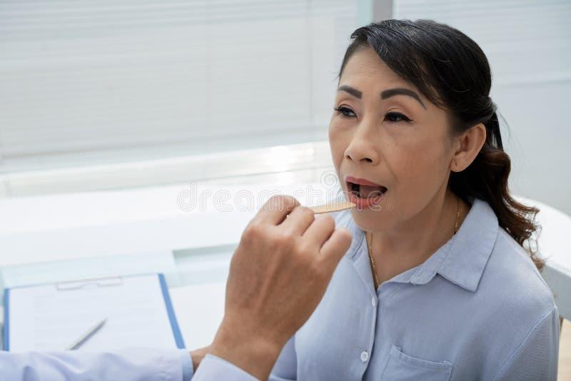 Patiënt die Keelonderzoek hebben stock foto's