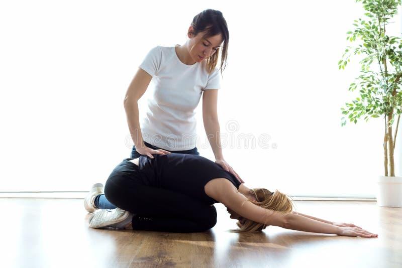 Patiënt die lichaamsbewegingen met zijn therapeut in fysioruimte doen stock afbeelding