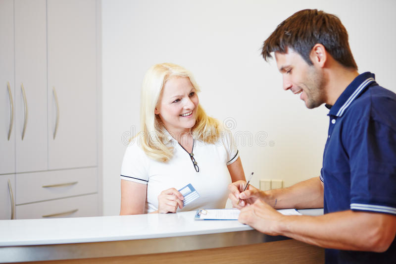 Patiënt die met artsenmedewerker bij ontvangst spreken stock afbeelding