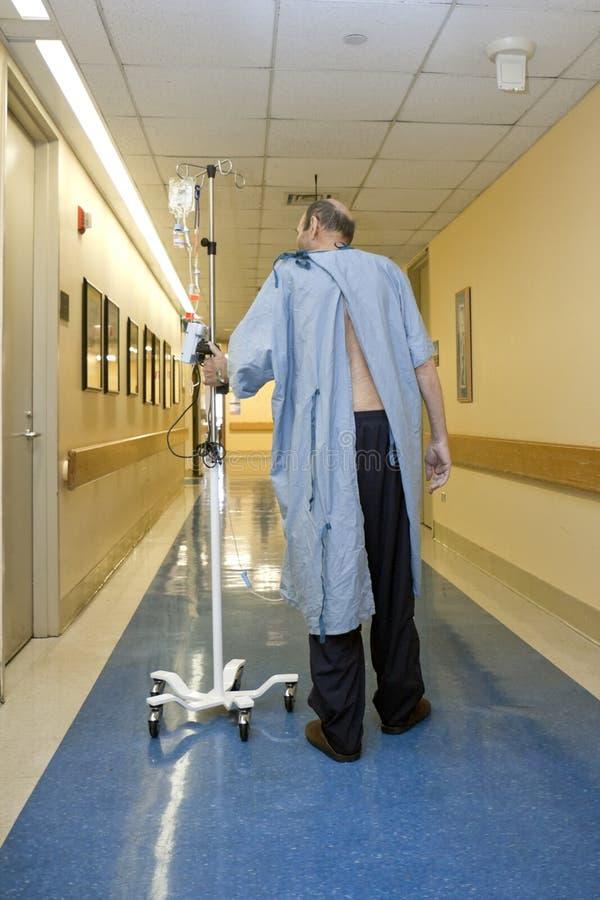 Patiënt die onderaan de het ziekenhuisgang loopt royalty-vrije stock foto's