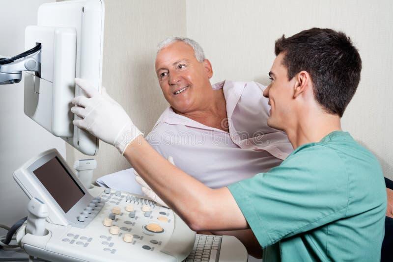 Patiënt die Ultrasone klankmachine bekijken stock foto's