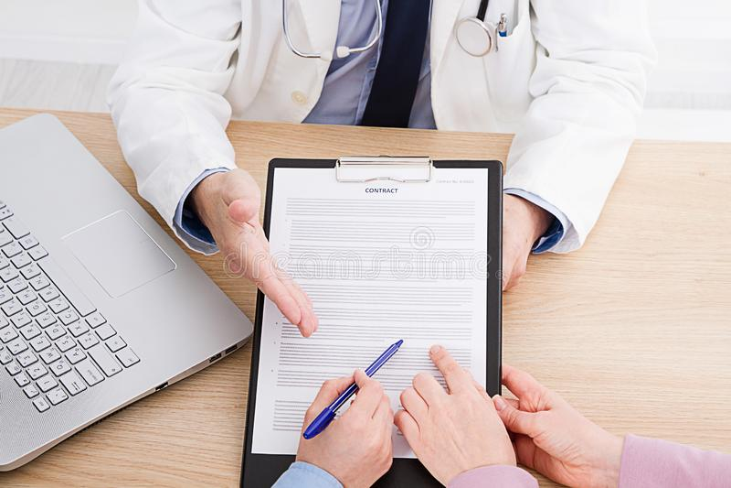 Patiënt die vastbesloten aan een mannelijke arts luisteren die geduldige symptomen verklaren of een vraag stellen aangezien zij a stock foto