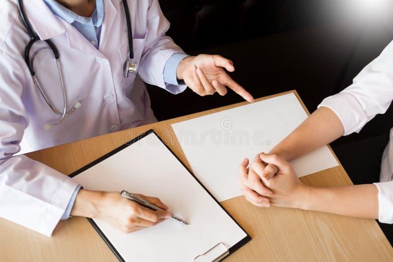Patiënt die vastbesloten aan een mannelijke arts luisteren die geduldige symptomen verklaren of een vraag stellen aangezien zij a stock fotografie