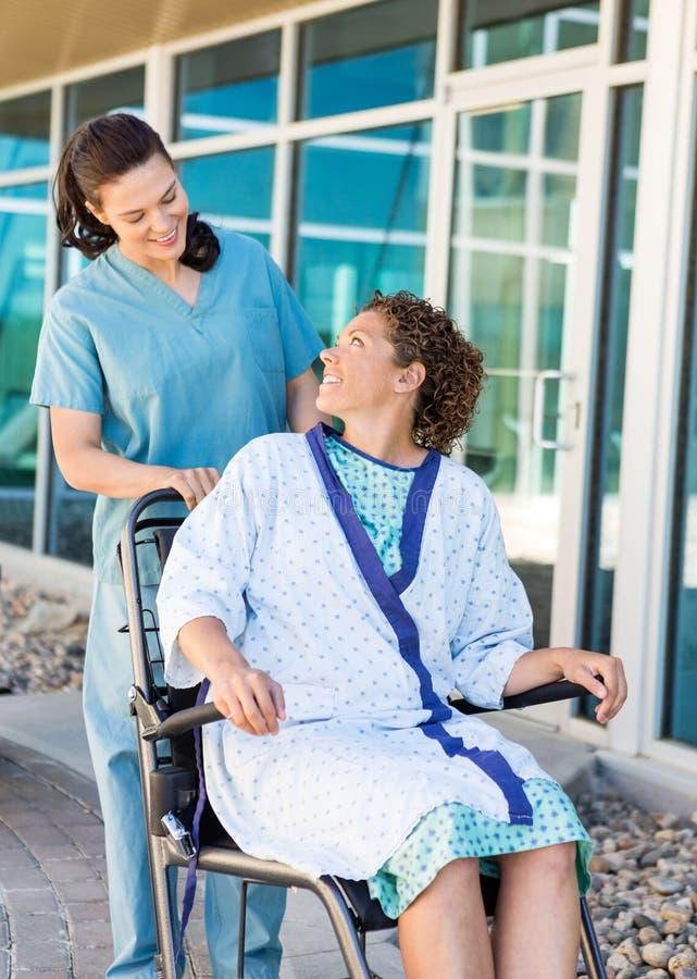 Patiënt die Vriendschappelijke Verpleegster While Sitting On bekijken stock afbeeldingen