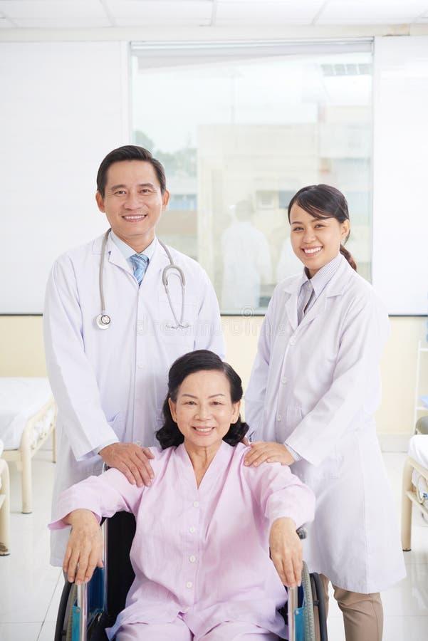 Patiënt en artsen stock afbeeldingen