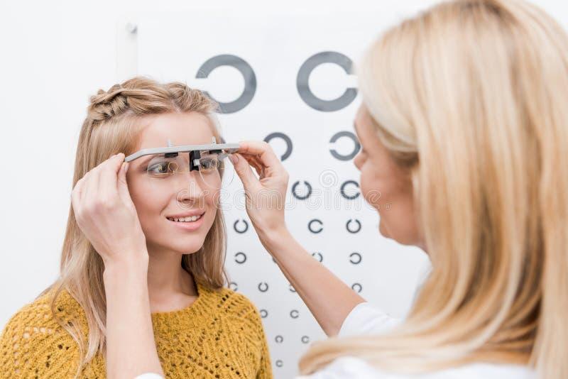 patiënt en oogarts met proefkader en oog stock afbeeldingen