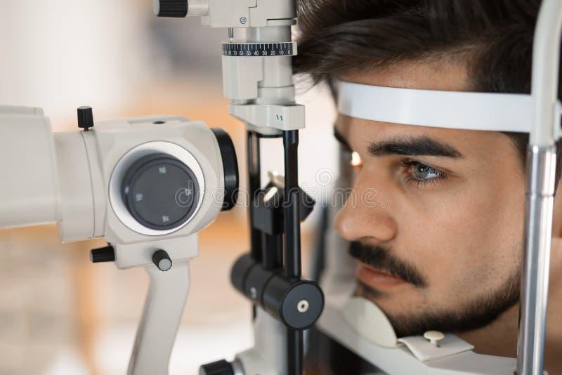 Patiënt of klant bij spleetlamp bij optometrist of opticien stock foto's