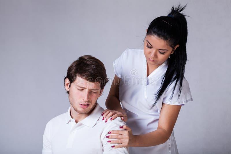 Patiënt met pijnlijke schouder stock afbeeldingen