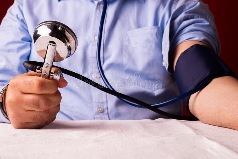 Patiënt met te hoge bloeddruk een bloeddruk autotest uitvoeren/mens die royalty-vrije stock foto's