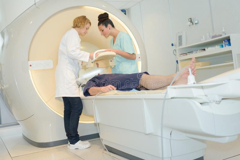 Patiënt op mrimachine terwijl twee vrouwelijke artsen die het in werking stellen royalty-vrije stock fotografie
