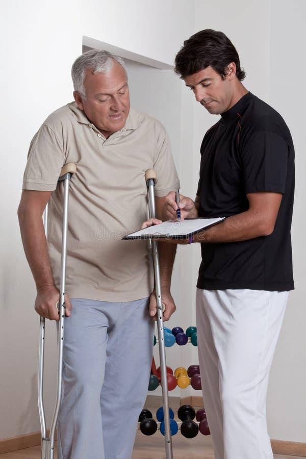 Patiënt op Steunpilaren en Arts stock fotografie