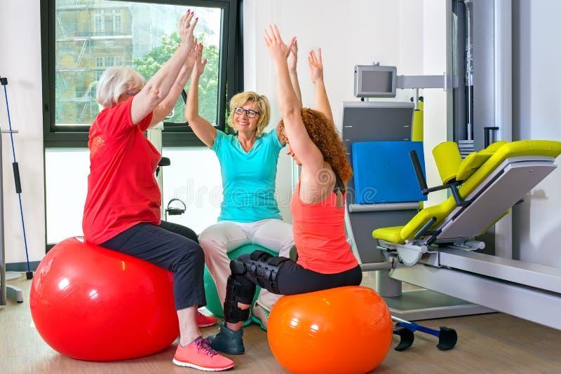 Patiënten op stabiliteitsballen die oefeningen doen stock afbeeldingen