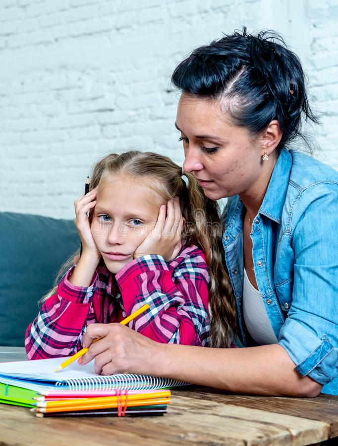 Patience mum with daughter unable to concentrate whilst doing homework sitting on sofa at home in learning difficulties homework royalty free stock photo