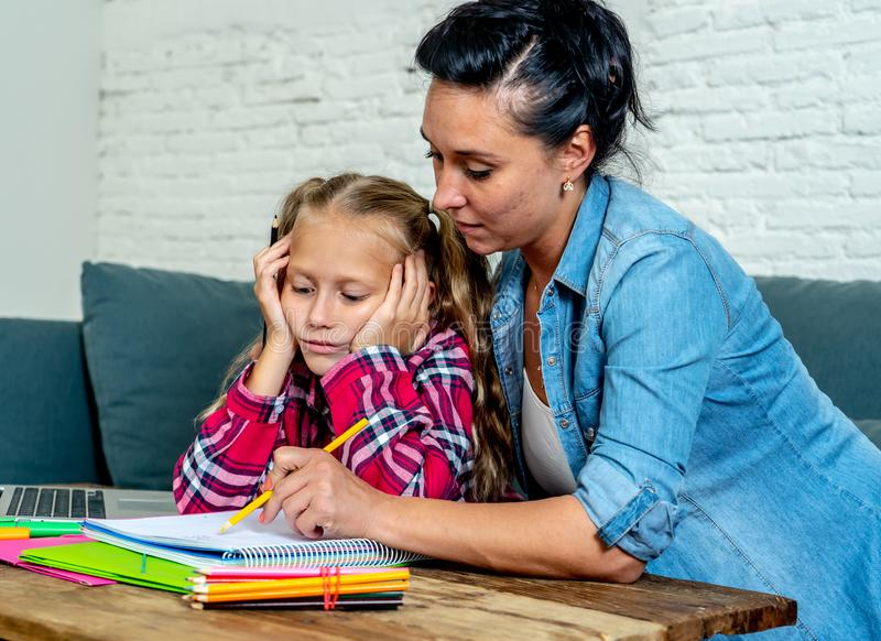 Patience mum with daughter unable to concentrate whilst doing homework sitting on sofa at home in learning difficulties homework stock images