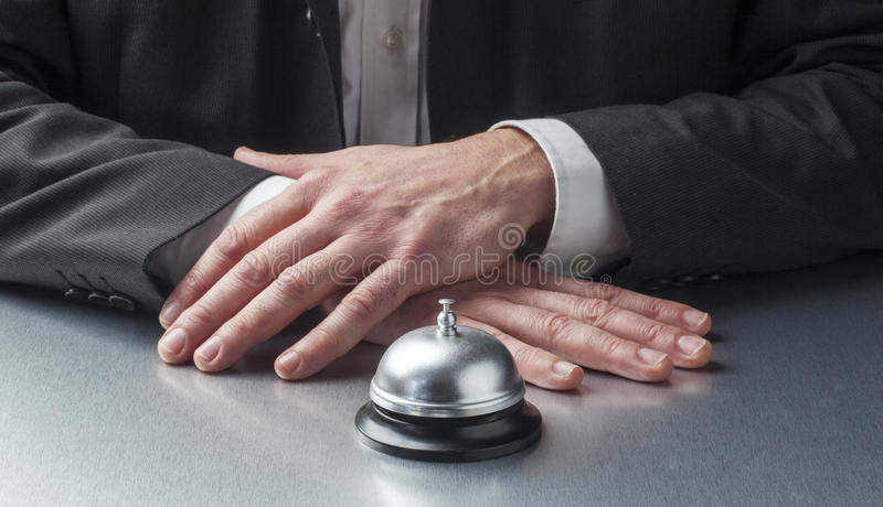 Patience in service industry. Calm professional in front of bell waiting for signal of assistance stock photography