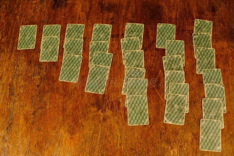 Patiens av att spela kort på en trätabell fotografering för bildbyråer