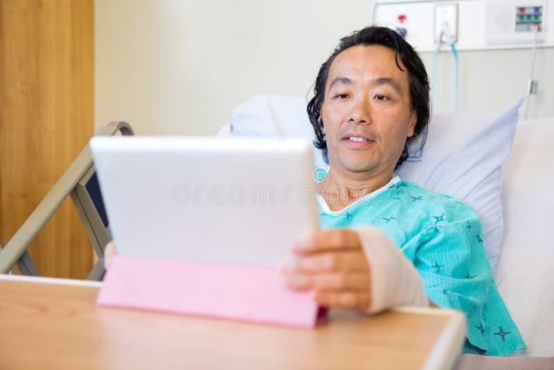 Patient à l'aide de la Tablette de Digital tout en reposant dessus image libre de droits