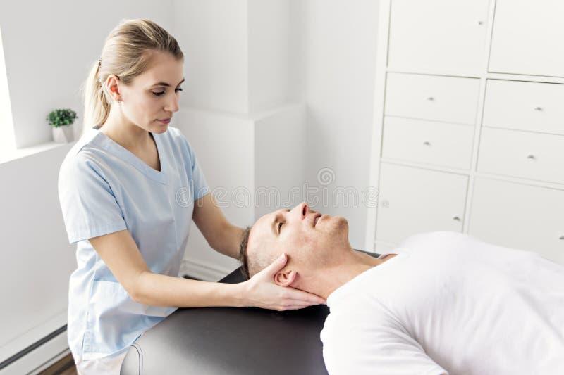 Patient à la physiothérapie faisant des exercices physiques avec son thérapeute photographie stock