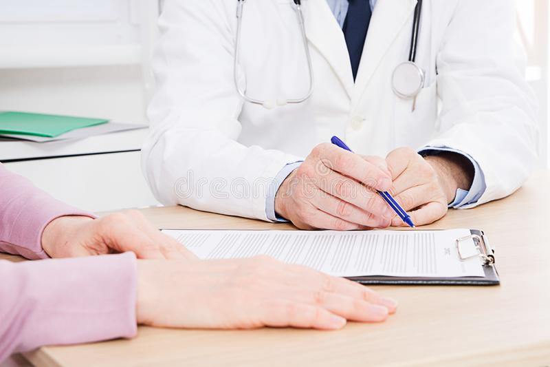 Patient écoutant attentivement un docteur masculin expliquant des symptômes patients ou posant une question comme ils discutent d photos libres de droits