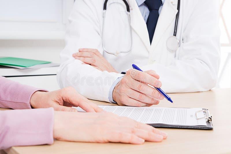 Patient écoutant attentivement un docteur masculin expliquant des symptômes patients ou posant une question comme ils discutent d photographie stock libre de droits