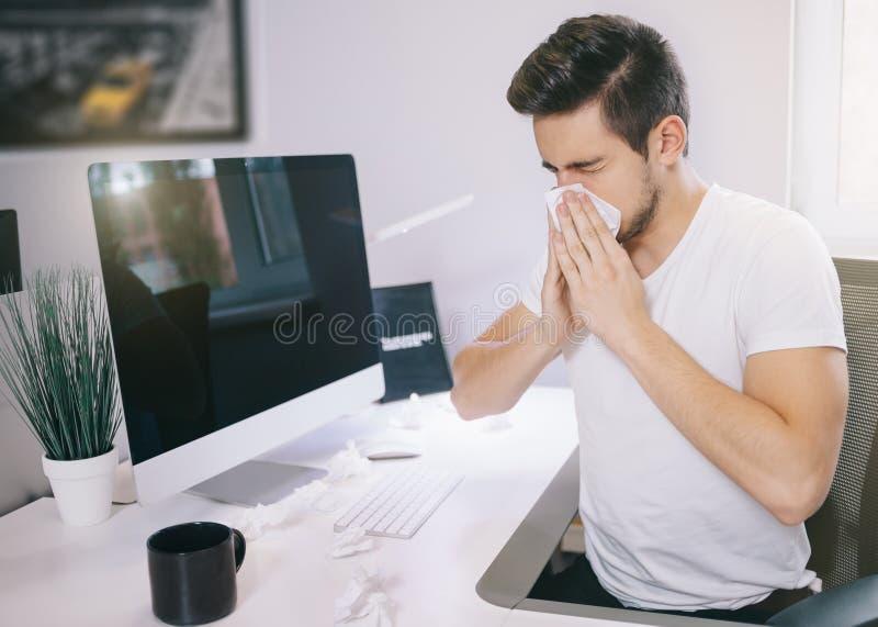 patient& x27的侧视图; s雇主 打喷嚏入一个组织在窗口附近的一个办公室在计算机 自由职业者 图库摄影