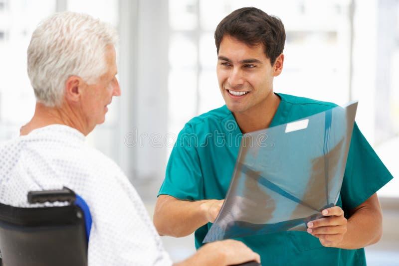 Patient aîné avec le jeune docteur image libre de droits